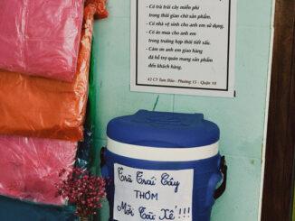 "A tea shop in Saigon hangs a sign ""share the rain"" with shipper"